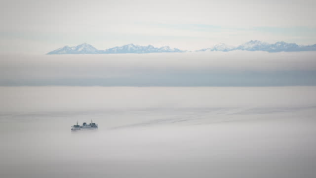 A winter daytime time lapse of two passing ferries appearing and disappearing in heavy fog with the Olympic mountains in the background