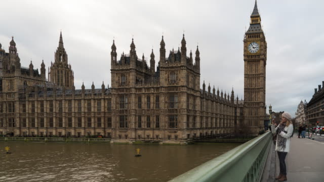 A winter daytime time lapse with heavy cloud cover from Westminster bridge in London, UK, focused on the Palace of Westminster and Elizabeth Tower (aka, Big Ben) featuring tourists crossing the bridge
