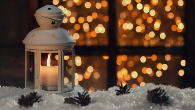 winter decoration with a candlestick near the snow-covered window - christmas decoration stock videos & royalty-free footage