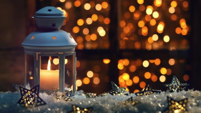 winter decoration with a candlestick near the snow-covered window - lanterna attrezzatura per illuminazione video stock e b–roll