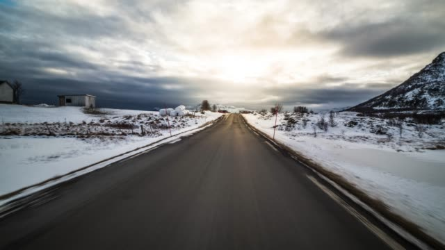 pov winter driving on country road in norway - back lit video stock e b–roll
