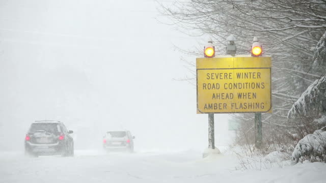 winter driving snow blizzard - hazardous area sign stock videos & royalty-free footage
