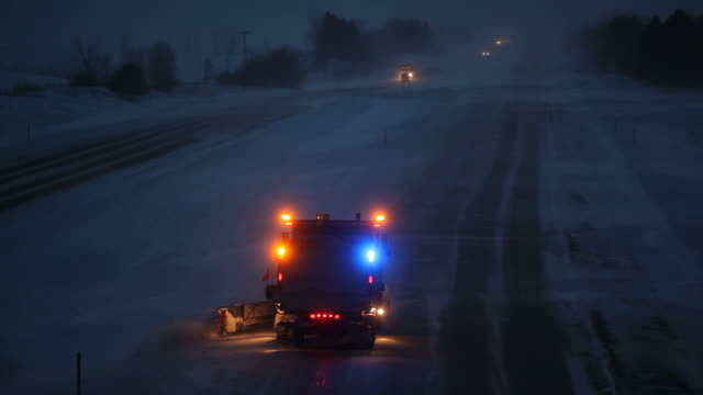 winter evening interstate highway with blowing snow and plow - snowplough stock videos & royalty-free footage
