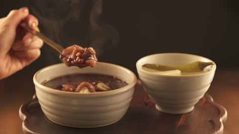 vídeos y material grabado en eventos de stock de winter food - dongchimi(radish water kimchi) in bowl and hand scooping patjuk(red bean soup) with spoon - comida coreana