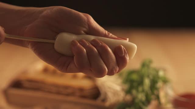 vídeos y material grabado en eventos de stock de winter food - hand sticking wooden skewer into garaetteok(bar rice cake) - comida coreana