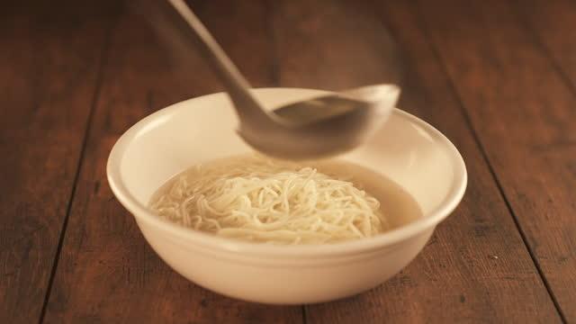 vídeos y material grabado en eventos de stock de winter food - meat stock being poured in bowl with plain noodles - cucharón