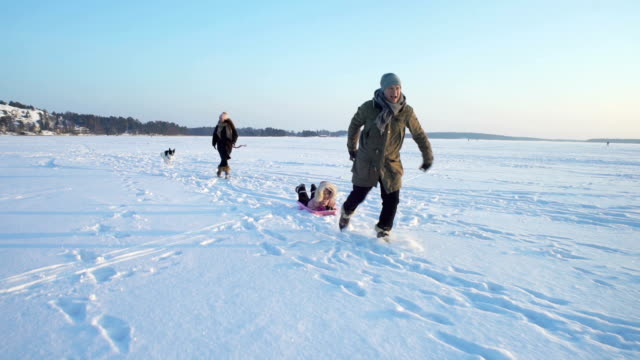Winter fun, snow, family sledding with dog at winter time