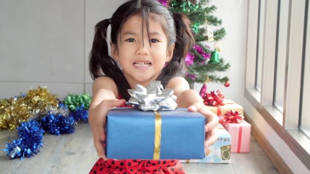 winterurlaub-traditionen: kleine asiatin lächeln und abhaltung geschenkbox - weihnachtsgeschenk stock-videos und b-roll-filmmaterial