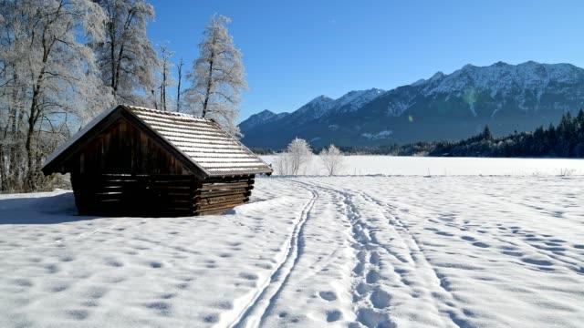 winter landscape with snowshoe trails and haystack near frozen lake barmsee, krün, garmisch-partenkirchen upper bavaria, bavaria, germany, european alps - krün stock videos and b-roll footage