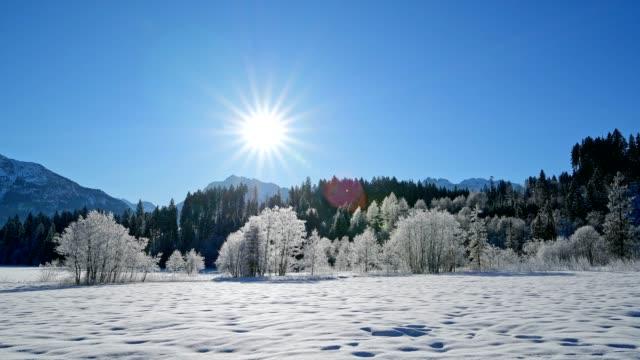 winter landscape with sun near lake barmsee, krün, garmisch-partenkirchen upper bavaria, bavaria, germany, european alps - krün stock videos and b-roll footage