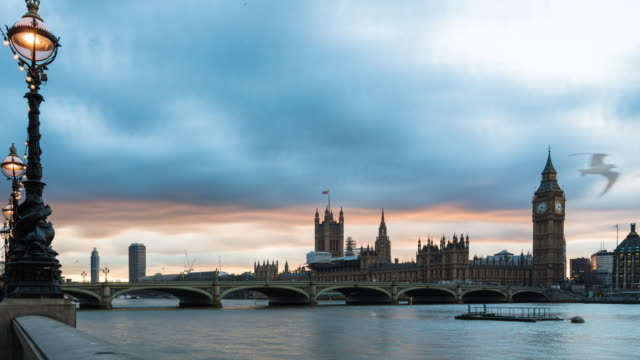 A winter late afternoon time lapse taken from the south bank of the Thames river (London, UK) featuring Westminster Palace, Elizabeth Tower (aka, Big Ben), and Westminster bridge with a street light turning on in the foreground