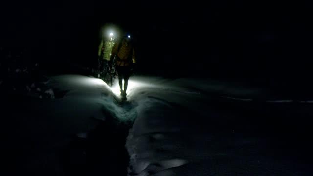 vídeos y material grabado en eventos de stock de aventura de montaña de invierno. una joven pareja en un sendero. noche - linterna