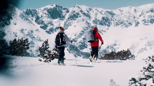 winter mountain adventure. young couple on a trail - sportswear stock videos & royalty-free footage