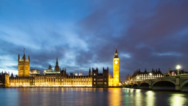 A winter nighttime time lapse of the Palace of Westminster in London, UK, taken from the south bank of the Thames River featuring the full south face of the palace, Elizabeth Tower (aka, Big Ben), and the Westminster bridge