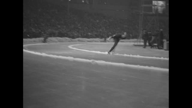 winter olympics in oslo / bislett stadium men's speed skating begins / skaters pass olympic flame / one skater stumbles and goes down / aerials of... - 1952 bildbanksvideor och videomaterial från bakom kulisserna