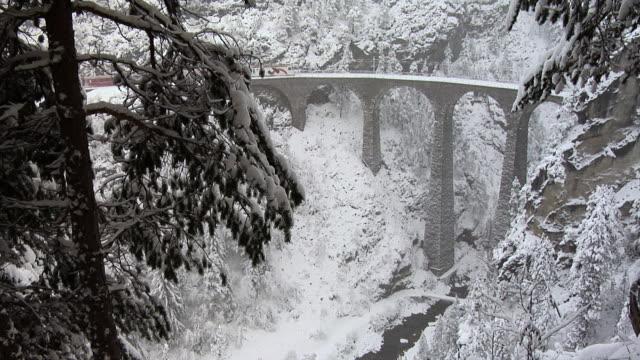 winter on the albula railway. train on the famous landwasser viaduct - viaduct stock videos & royalty-free footage