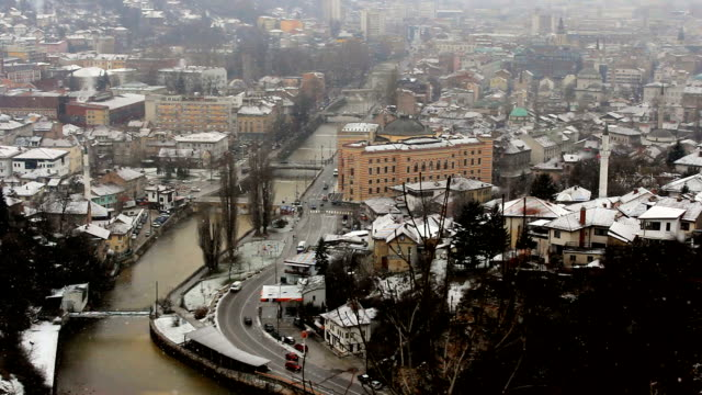 Winter river city panorama with snow falling.