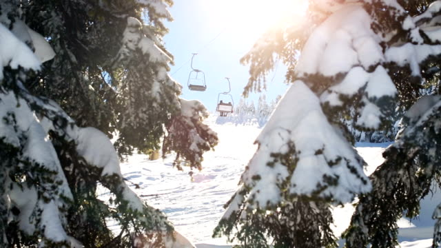 winter scene. sunbeams hitting the lens through snowy pine branches while ski lift passes at the background - stazione sciistica video stock e b–roll
