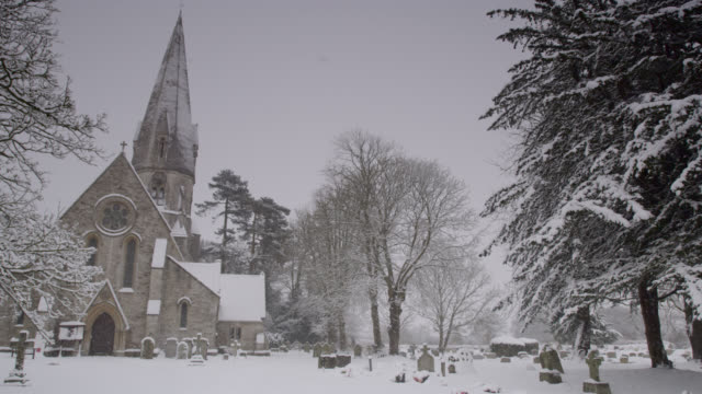 winter snow falls onto village church and graveyard, oxfordshire, england - snow stock videos & royalty-free footage