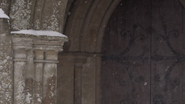 vidéos et rushes de winter snow falls onto village church, oxfordshire, england - ornement