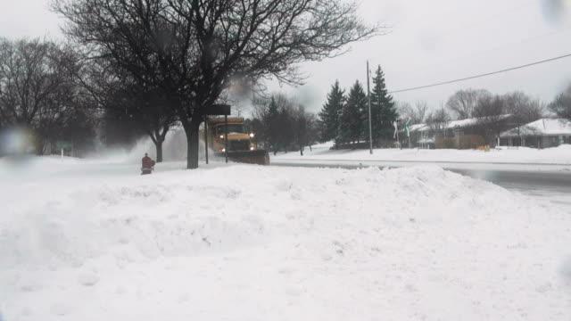 Winter snowstorm. Car traffic on slippery road. Snowplow.