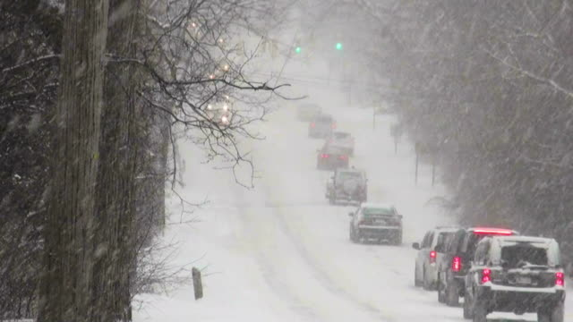 winter snowstorm. car traffic on slippery road. - sliding stock videos & royalty-free footage
