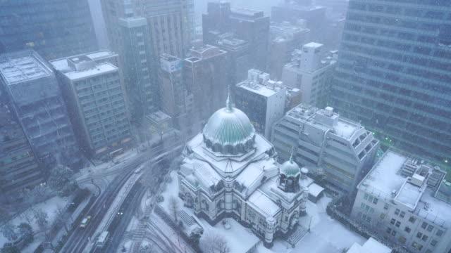winter snowstorm in ochanomizu chiyoda-ku tokyo japan – january. 22 2018. snow wraps up the nickolai cathedral (nikolai-do) and the neighboring buildings. - 見渡す点の映像素材/bロール
