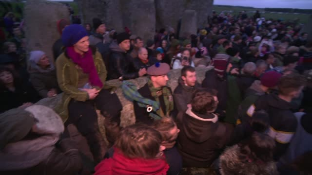 winter solstice celebrated at stonehenge; england: wiltshire: stonehenge: ext / night group of people shouting 'may there be peace in the east' sot... - solstice stock videos & royalty-free footage