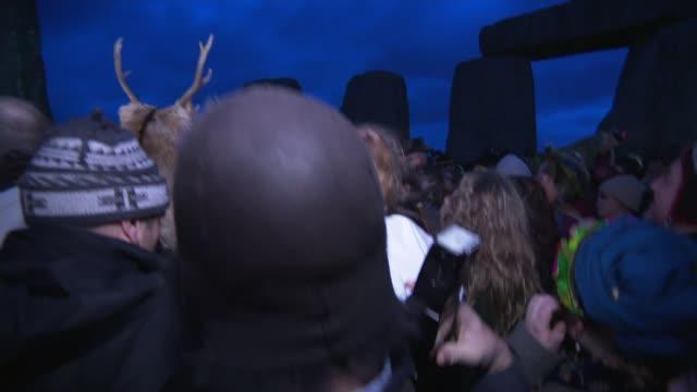Winter Solstice ceremony at Stonehenge **BEWARE Stonehenge Crowds of people at Stonehenge / banging of drums SOT / man in deer hat / crowd performing...