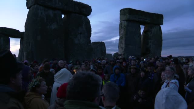 winter solstice marked at stonehenge; england: wiltshire: stonehenge: ext / dawn various of crowds gathered at stonehenge at dawn to mark winter... - solstice stock videos & royalty-free footage