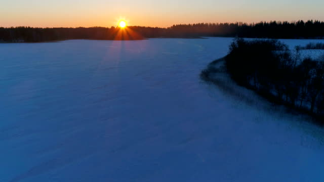 Winter sunrise over frozen lake