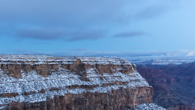 A winter sunrise time lapse of the Grand Canyon from the El Tovar Hotel's overlook on the South Rim of the Grand Canyon (Arizona, USA) panning down the canyon wall with light snow on the ground.