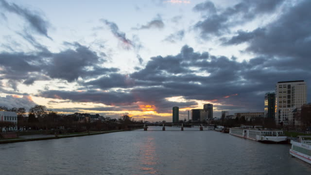 A winter sunset of the Main river from the Eiserner Steg (Iron Footbridge) in Frankfurt am Main, Germany, showing barge and ferry traffic on the water and clouds moving towards the camera