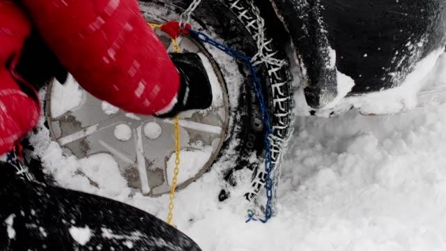 vidéos et rushes de pov. pneu d'hiver sur la route enneigée tout en neigeant. bel homme aîné actif mettant les chaînes de pneu dessus. sécurité routière en hiver. - roue