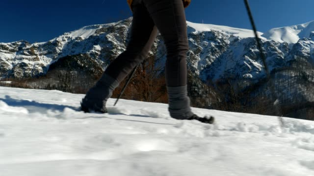 winter traveler, medium shot of one young woman tourist walking through deep snow, enjoying the winter mountain, portrait, winter sport, travel, exploration, adventure, tourism, determination, athlete, outdoors, mountain hiking, backpacker, alps - hiking pole stock videos and b-roll footage