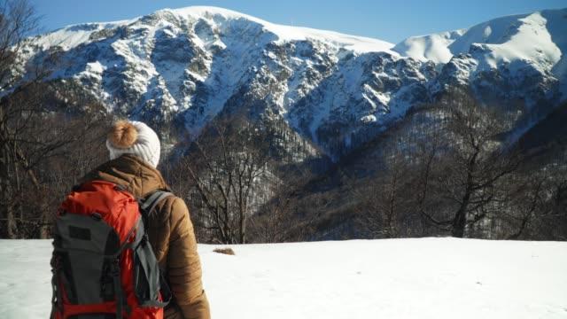 Winter Traveler, Medium Shot of One Young Woman Tourist Walking Through Deep Snow, Enjoying the Winter Mountain, Portrait, Winter Sport, Travel, Exploration, Adventure, Tourism, Determination, Athlete, Outdoors, Mountain Hiking,  Backpacker