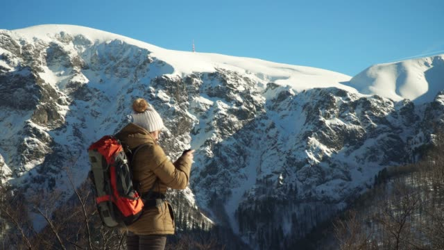 Winter Traveler, Selfie, Wide Shot of Young Woman Tourist Making Selfies and Taking Photos, Enjoying the Winter Mountain, Portrait, Winter Sport, Travel, Exploration, Adventure, Tourism, Athlete, Outdoors, Mountain Hiking, Backpacker, Alps