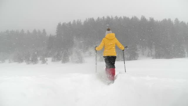 stockvideo's en b-roll-footage met winterreiziger. slow motion van een young woman tourist snowshoeing in de diepe sneeuw, genieten van de winter mountain. - sneeuwstorm