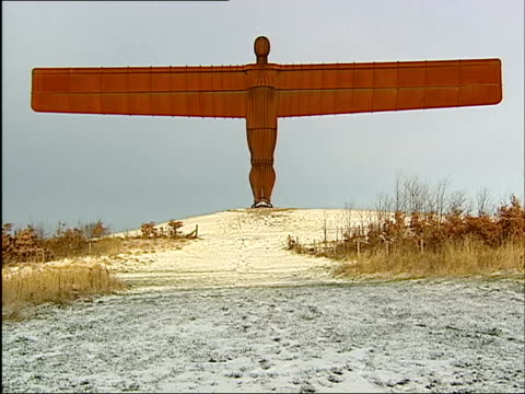 u'lay england tyne wear gateshead ext/snow la snow on ground at feet of angel of the north statue pull out scotland aberdeenshire snow plough... - angel of the north stock videos and b-roll footage