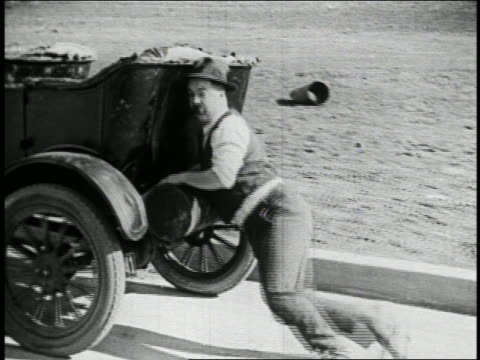 b/w 1925 (billy bevan) wiping brow + pushing group of cars bumper to bumper on road / feature - 1925 stock videos & royalty-free footage
