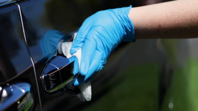 vidéos et rushes de essuyage vers le bas et désinfectant poignée de porte de voiture - clean