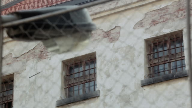 r/f wire fencing surrounding a peeling stone building with iron bars over its windows - iron bars for windows stock videos & royalty-free footage