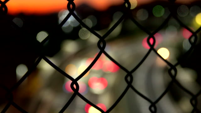 wire mesh (mesh fence) with city road highway at dusk - rete metallica filo metallico video stock e b–roll