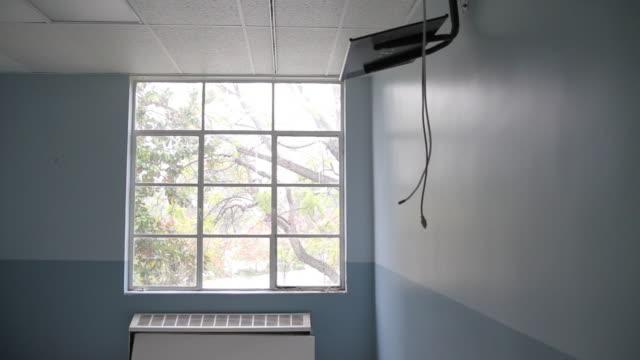 vídeos de stock, filmes e b-roll de wires dangle from empty tv shelf in patient room of closed hospital - falência