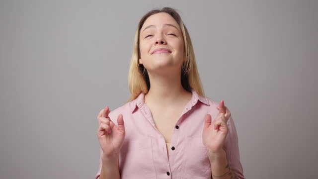 wishful woman in blouse with crossed fingers near grey wall - dishonesty stock videos & royalty-free footage
