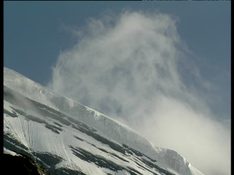 a wisp of white cloud moving slowly up snowy mountain slope switzerland - wispy stock videos and b-roll footage