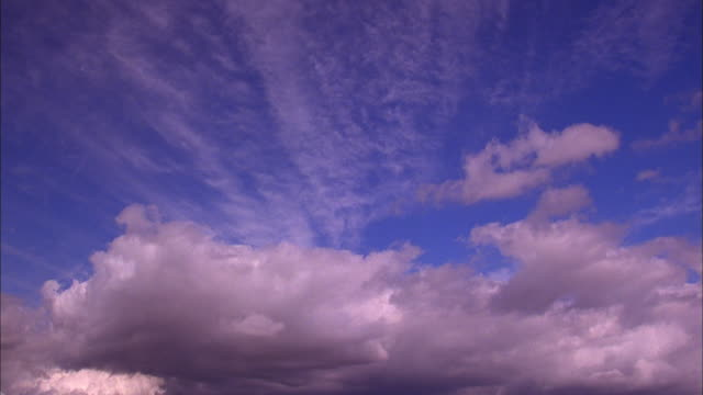 wispy cirrus clouds above billowing cumulus clouds in blue sky available in hd. - wispy stock videos and b-roll footage