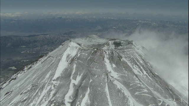 Wispy clouds billow around the snowy crater at the summit of Mt. Fuji.