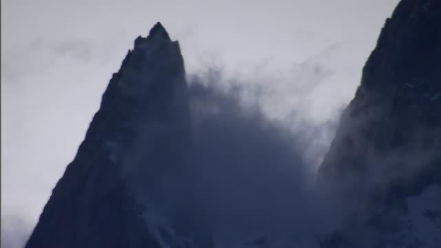 wispy clouds drift between mountain pinnacles. - mountain peak stock videos & royalty-free footage