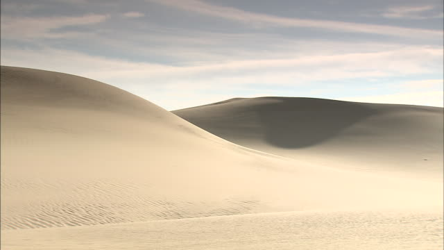 wispy clouds drift over barren desert sand dunes. - wispy stock videos & royalty-free footage